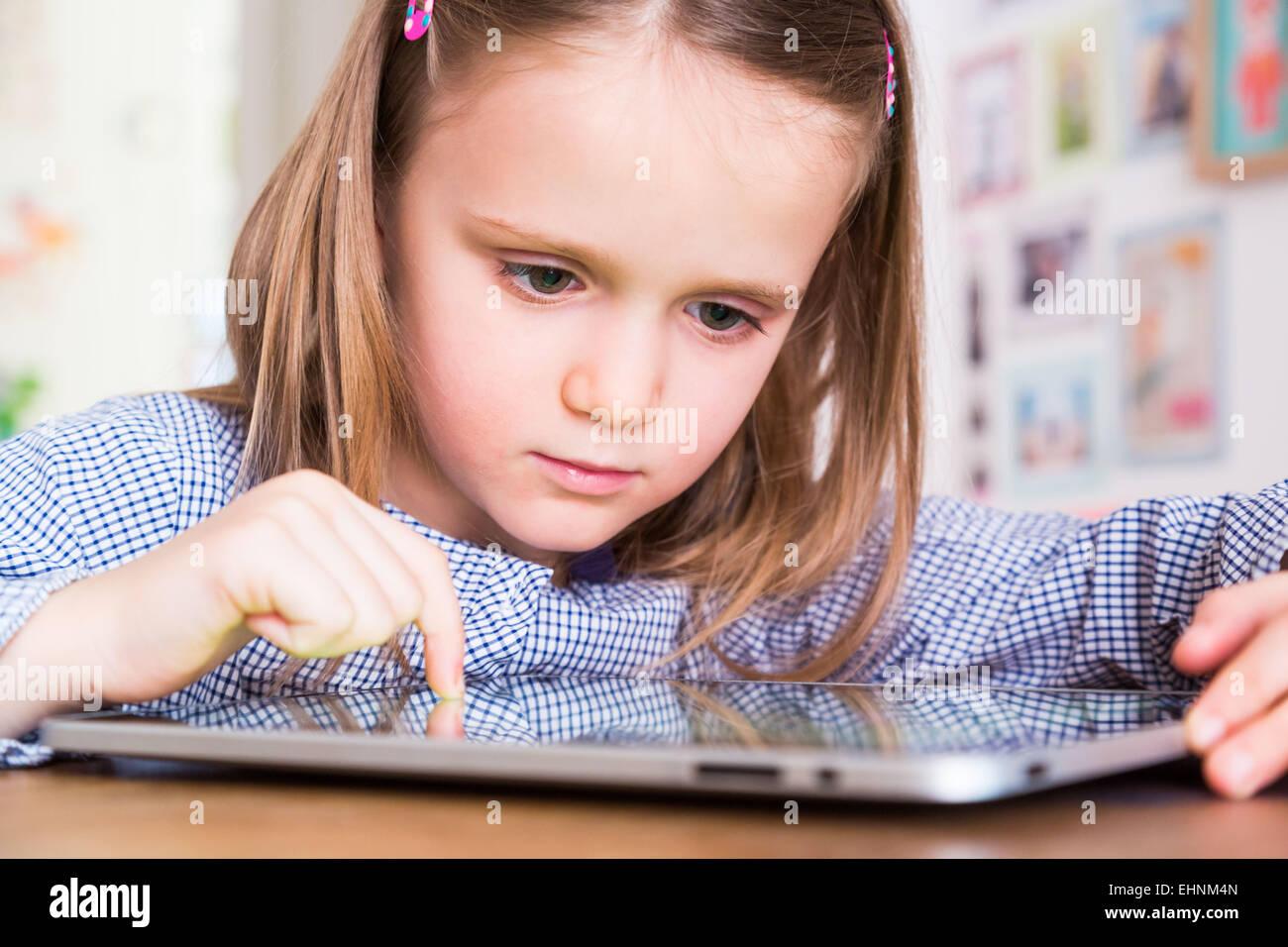 5 anno-vecchia ragazza utilizzando computer tablet. Immagini Stock