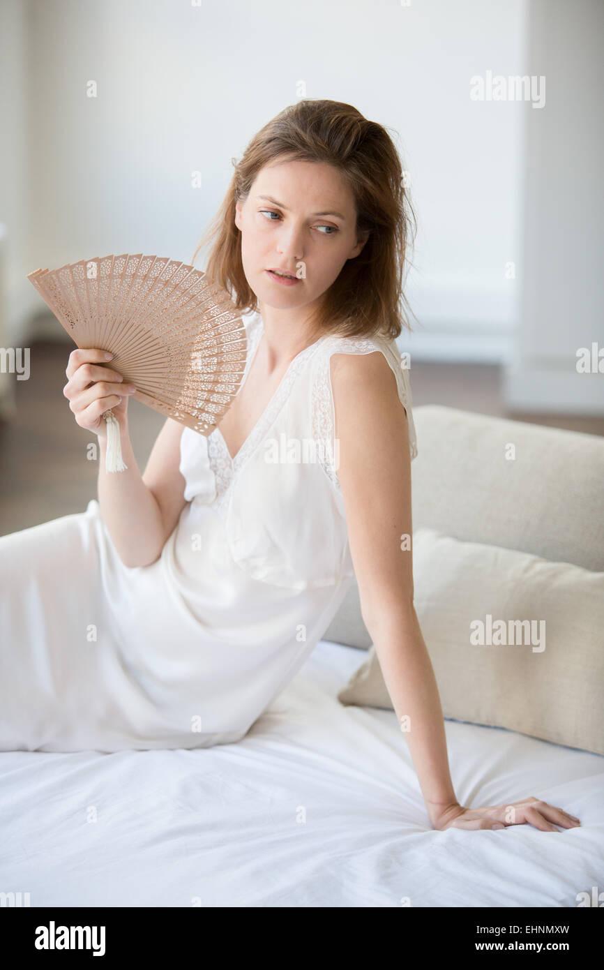 La donna il raffreddamento il suo volto con una ventola. Immagini Stock
