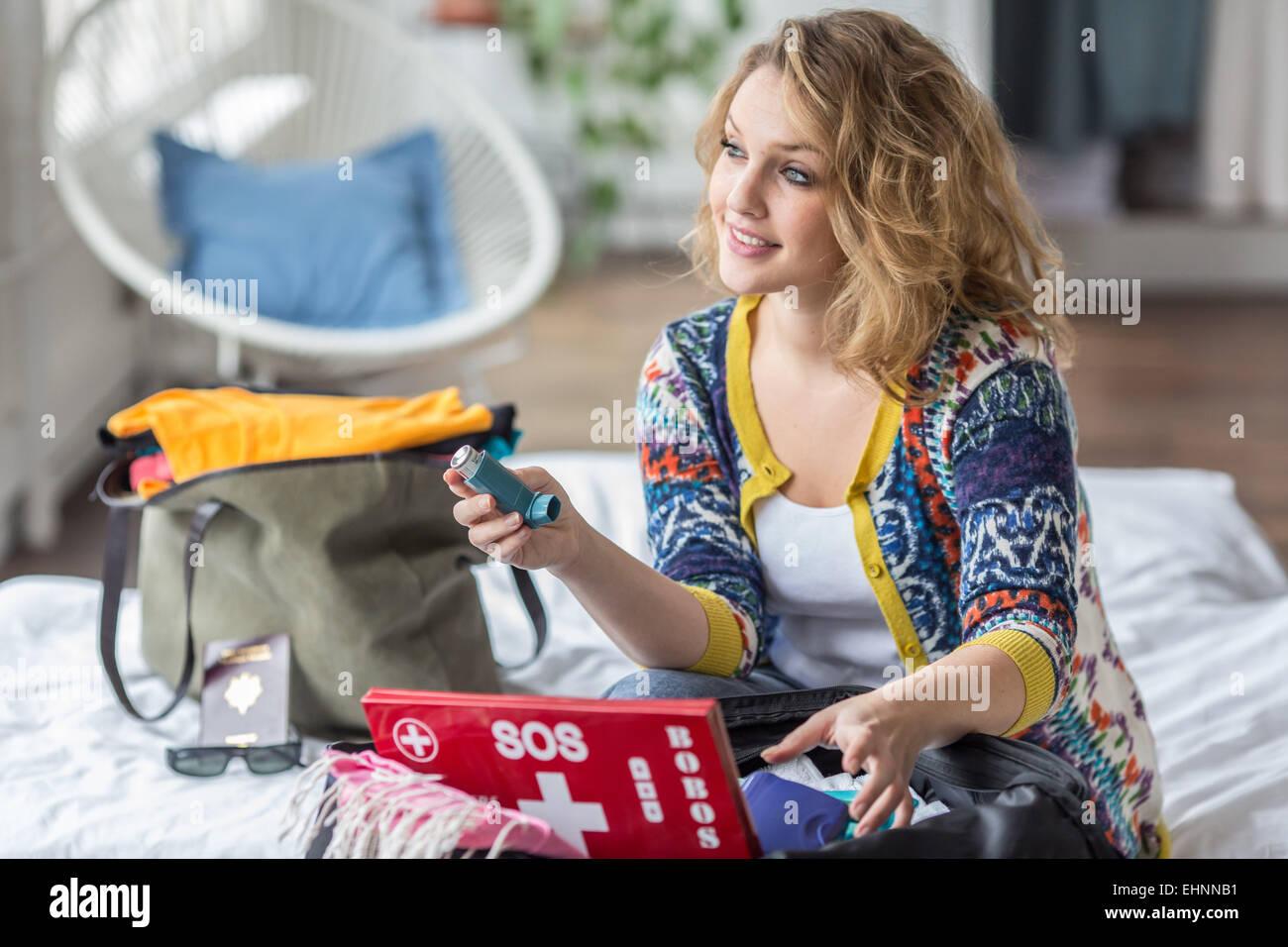 Donna preparare un primo aiuto kit medici compresi il trattamento di asma. Immagini Stock