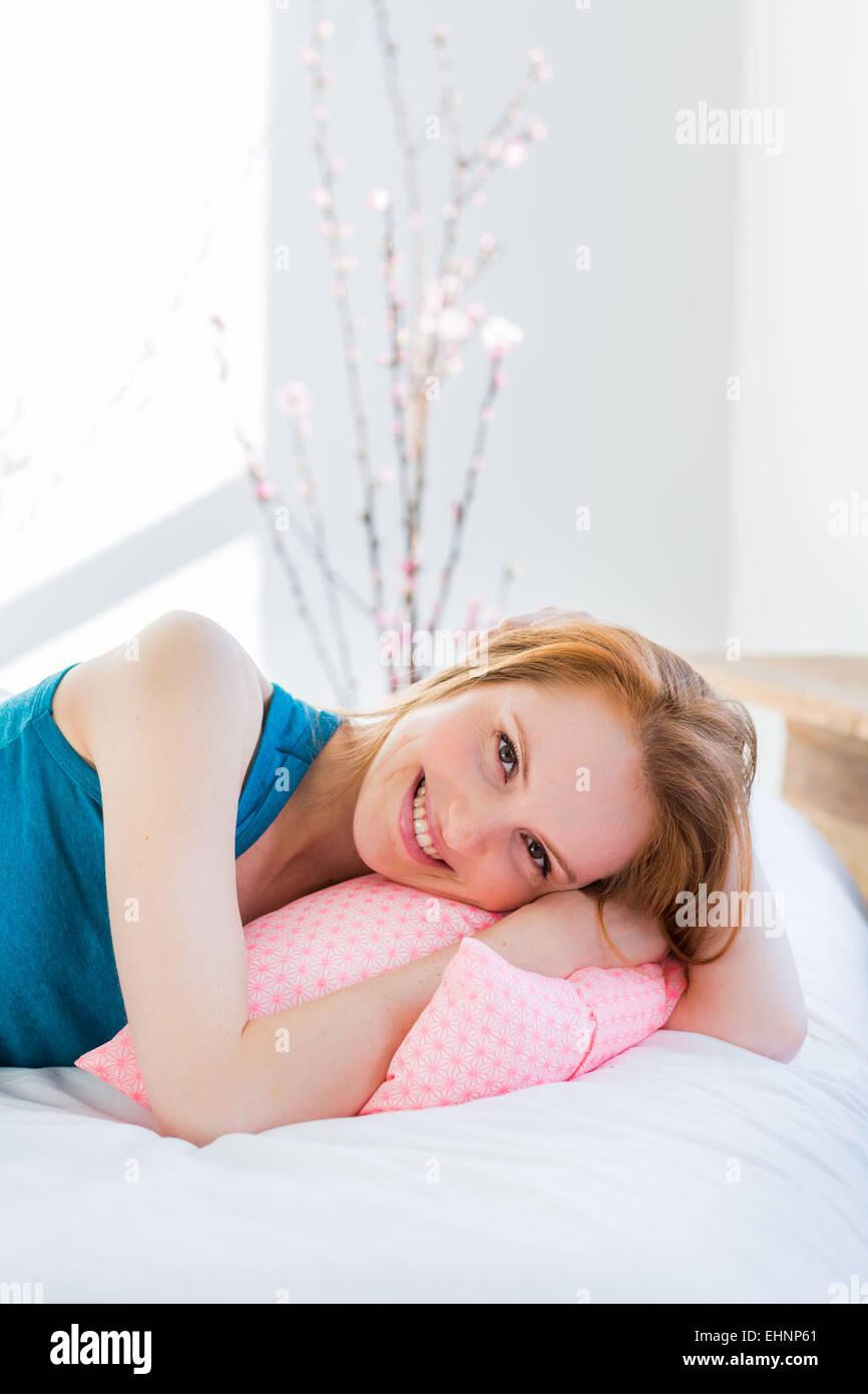Giovane donna giaceva a letto. Immagini Stock