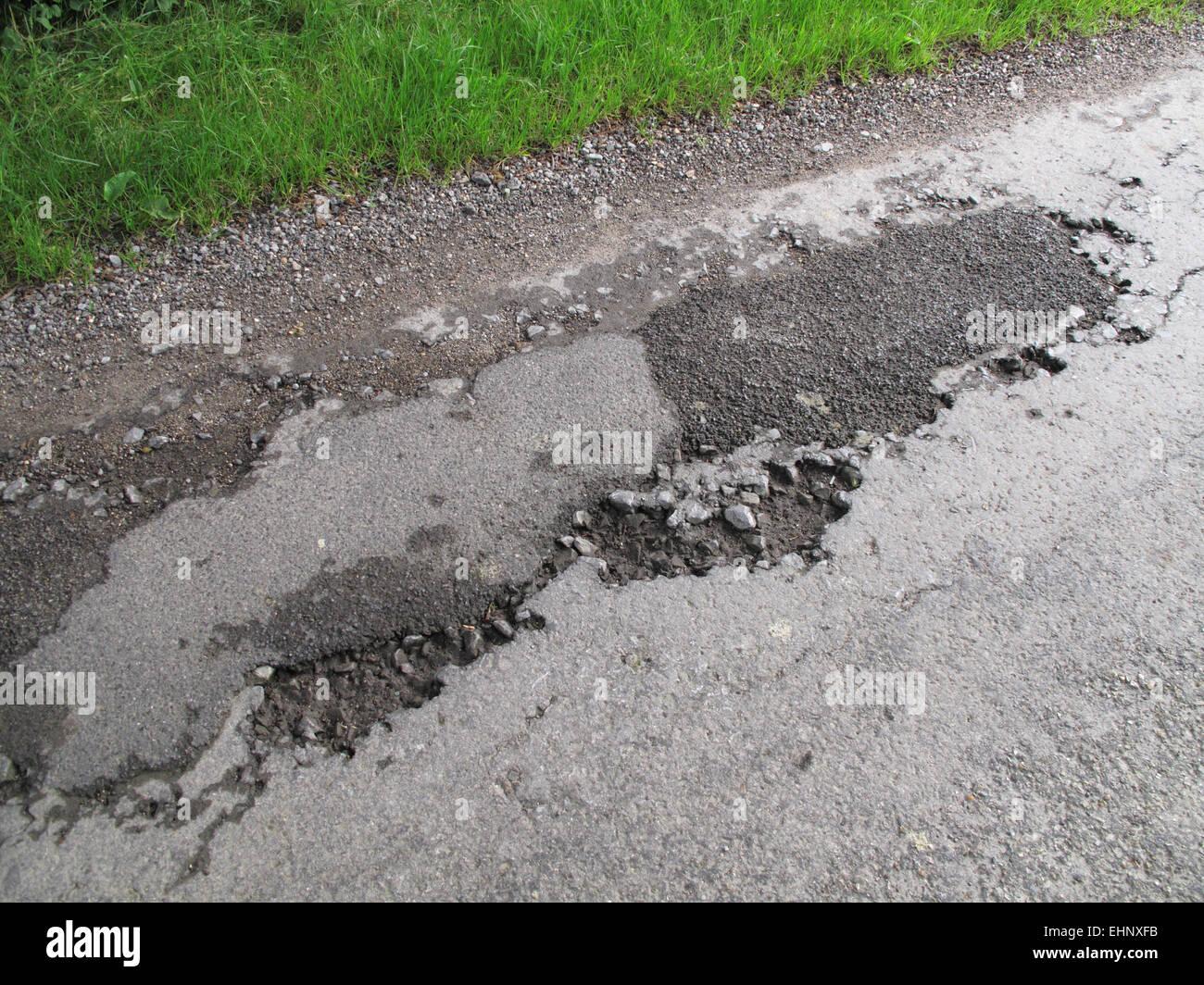 Buche in rottura di asfalto stradale del paese non marcati e pericoloso, Berkshire, Luglio Immagini Stock