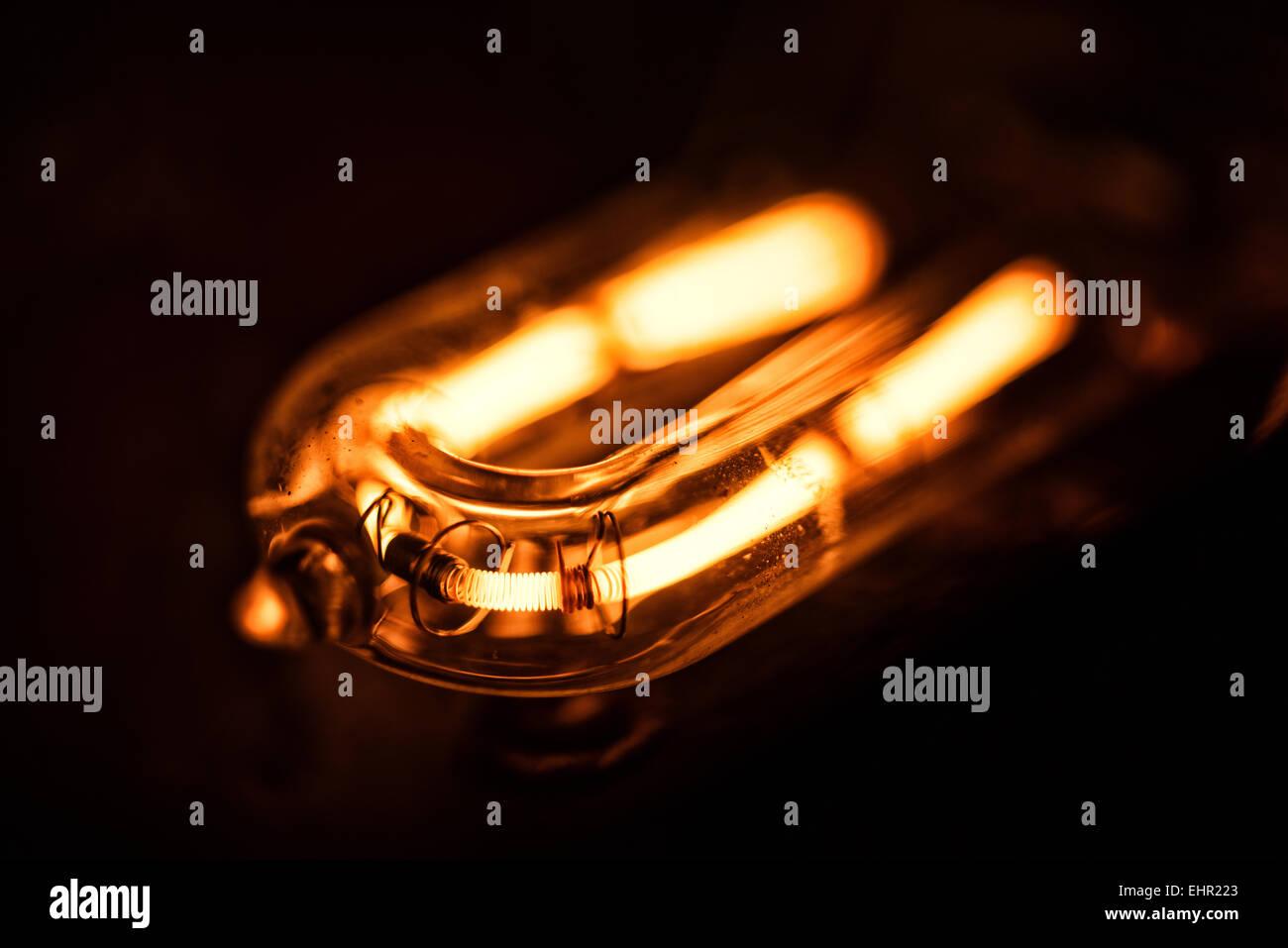 Il filamento incandescente di una 1000 lampada alogena al quarzo con scaglie di metallo e danni termici al riflettore Immagini Stock