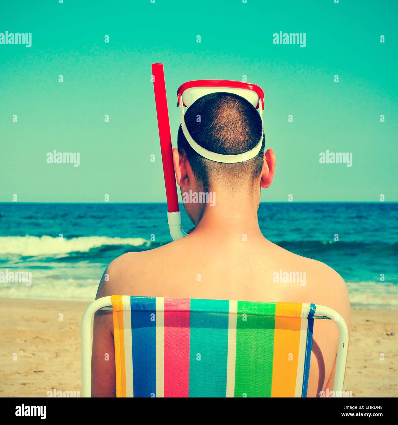 Foto dal retro di un uomo che indossa una maschera subacquea e un boccaglio seduto in una sedia a sdraio sulla spiaggia, Immagini Stock