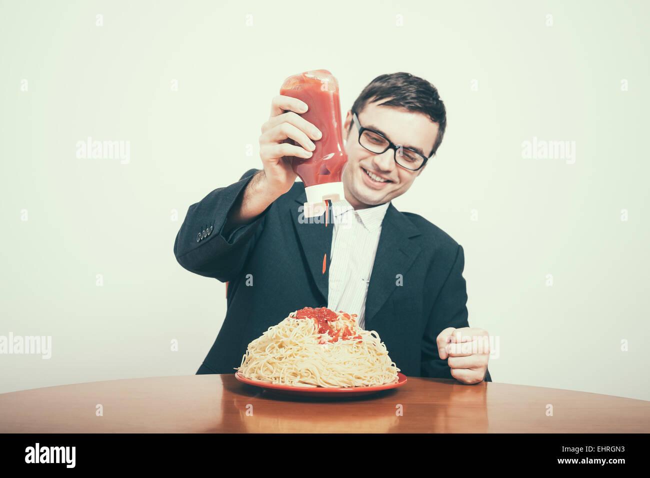 Felice il consumismo concetto. Happy businessman versando il ketchup su un enorme piatto di pasta. Immagini Stock