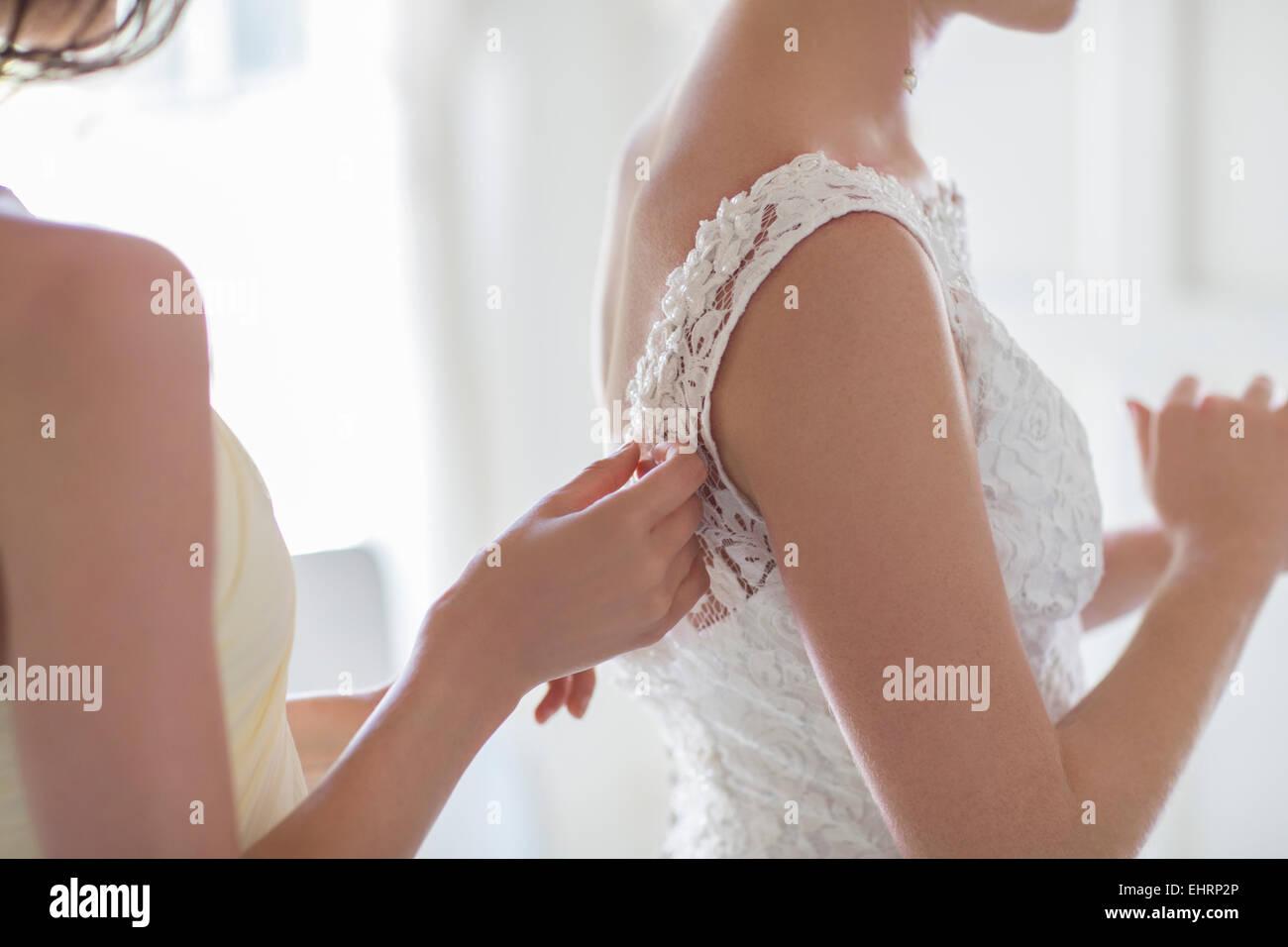 Damigella aiutando sposa con una medicazione in ambiente domestico Immagini Stock