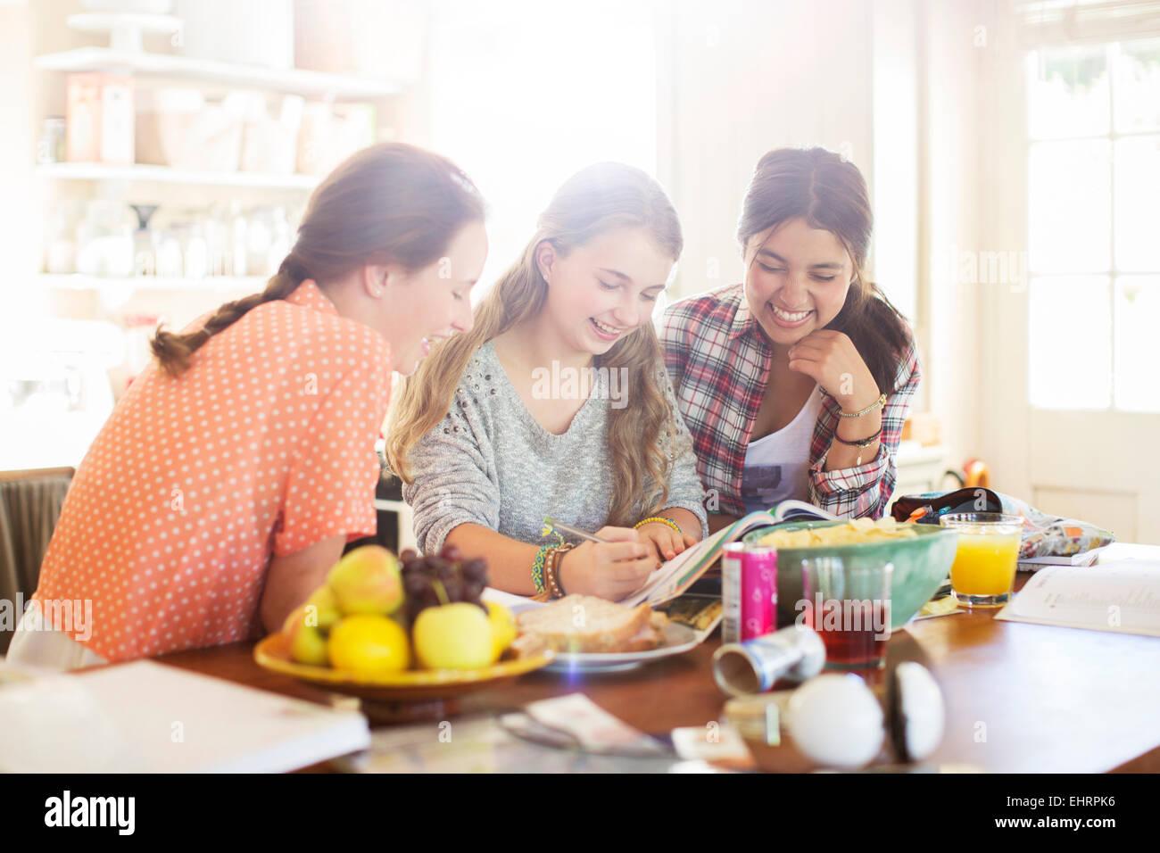 Tre ragazze adolescenti imparare a tavola in sala da pranzo Immagini Stock