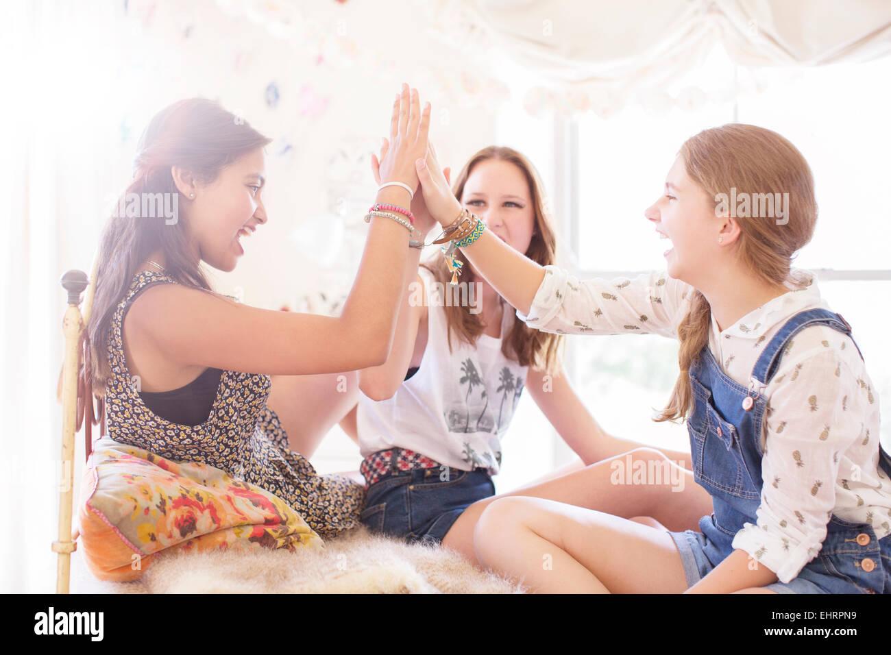Tre ragazze adolescenti facendo alta cinque sul letto Immagini Stock
