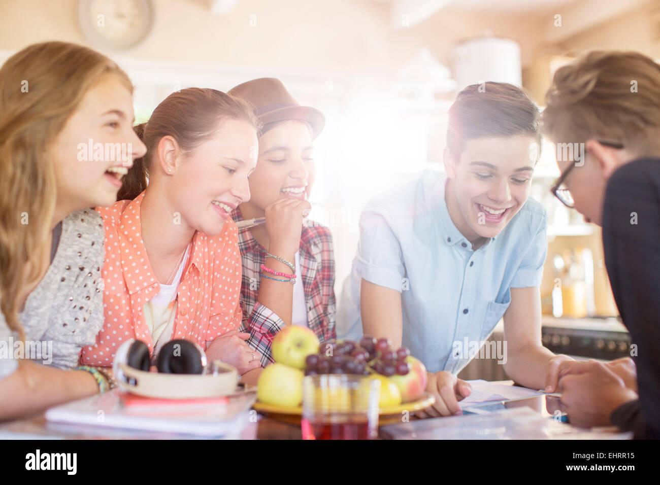 Un gruppo di ragazzi sorridenti riuniti intorno al tavolo nella sala da pranzo Immagini Stock