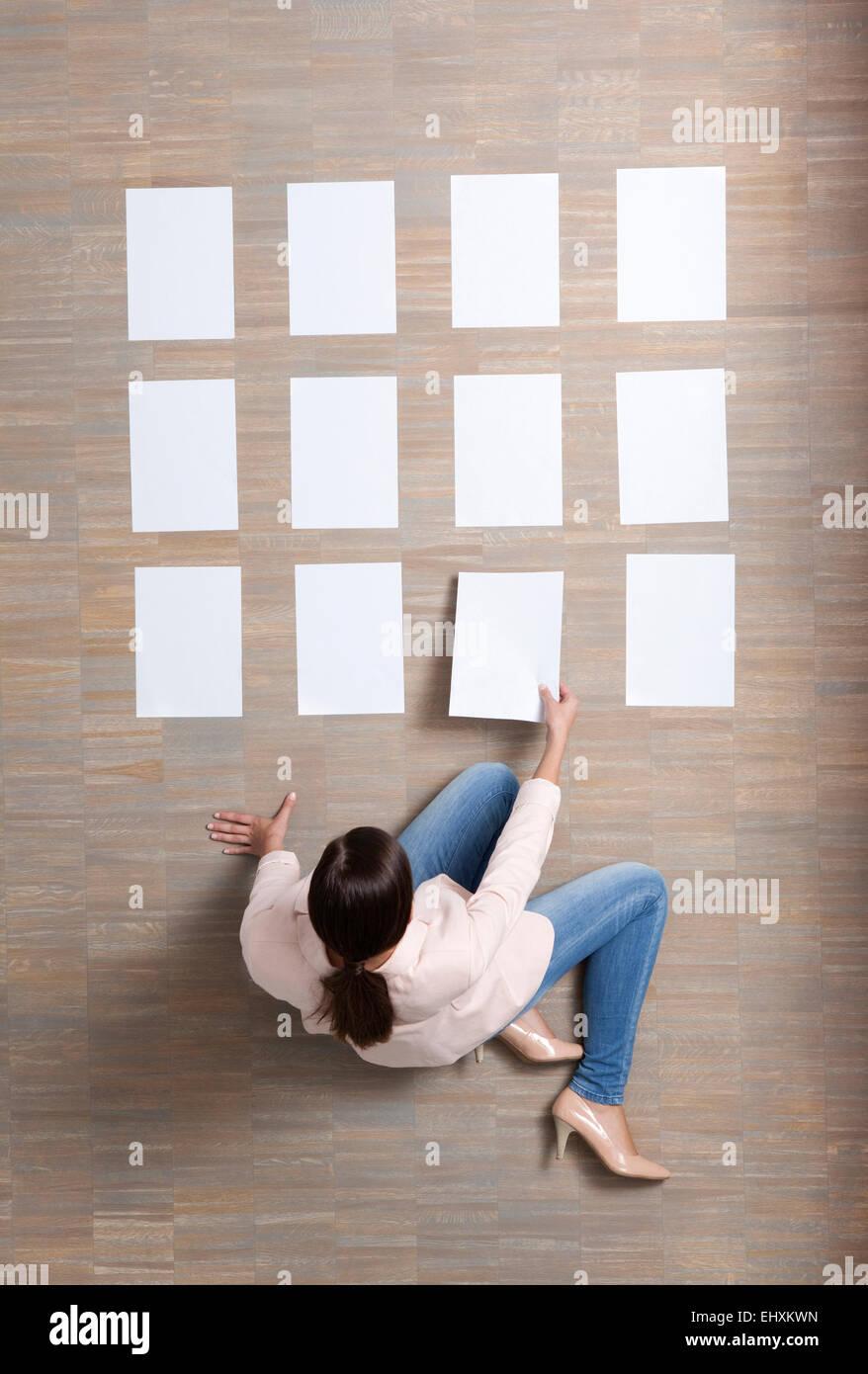 Imprenditrice seduta sul pavimento organizzando dei fogli bianchi Immagini Stock