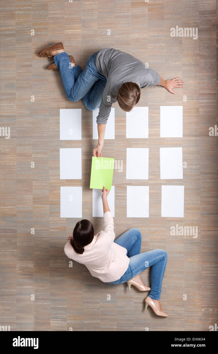 Imprenditore e imprenditrice seduta sul pavimento organizzando dei fogli bianchi Immagini Stock