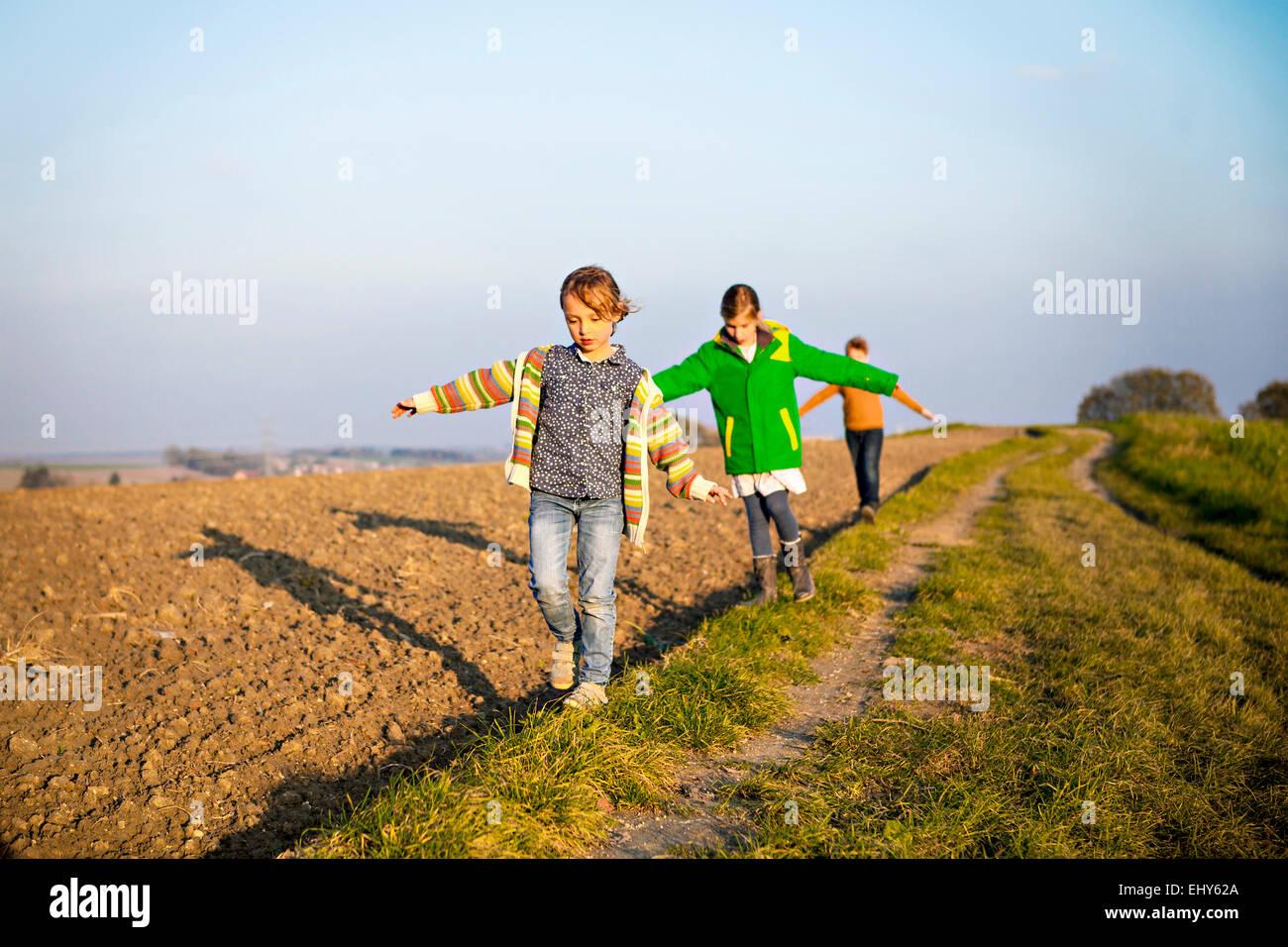 Tre bambini che giocano all'aperto Immagini Stock