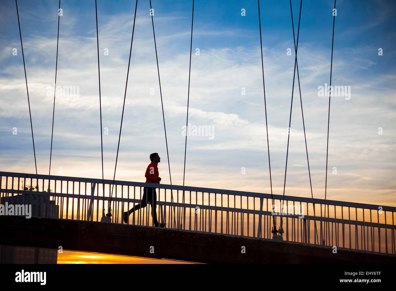 Uomo di jogging sul ponte al tramonto Immagini Stock