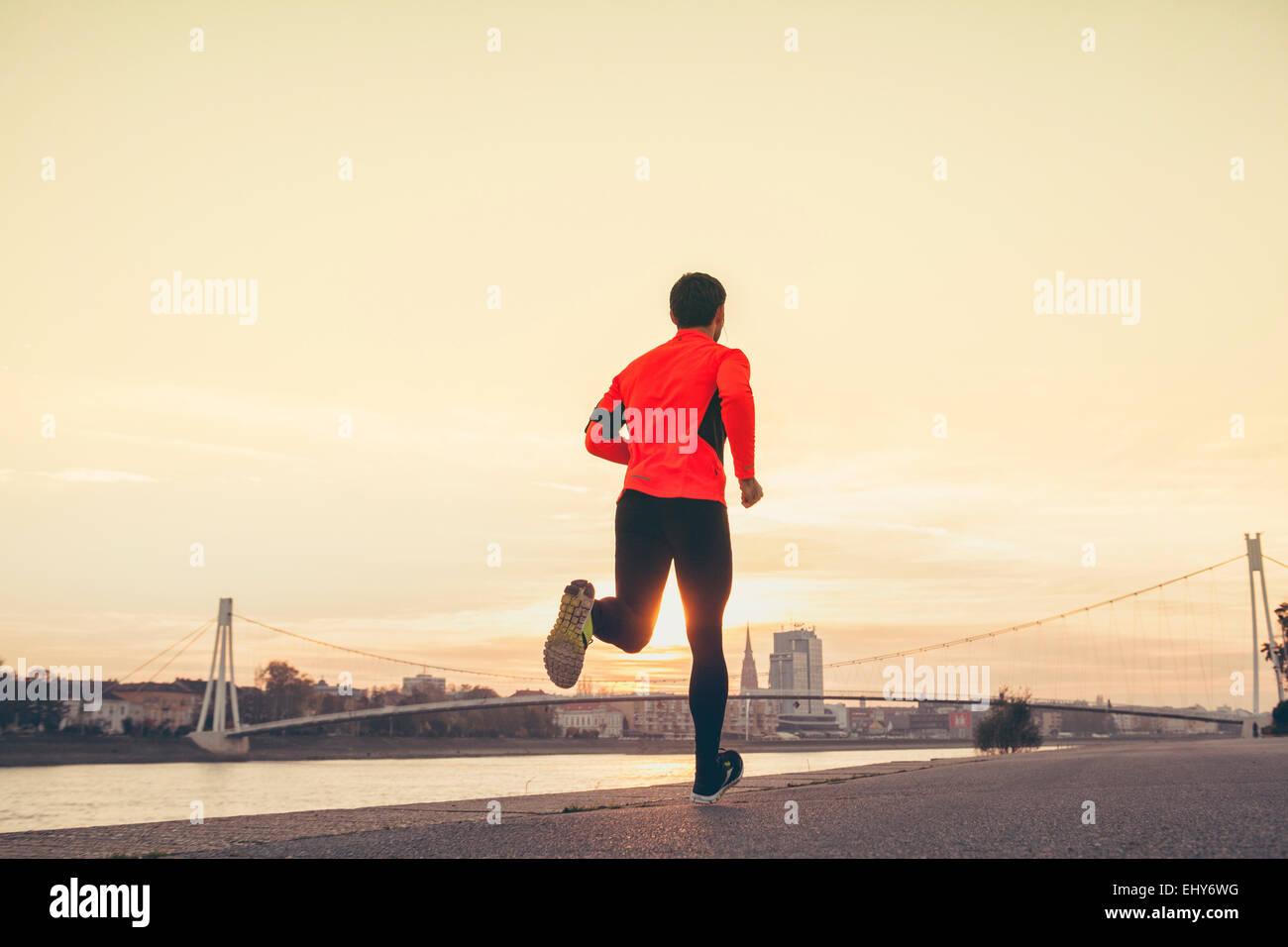 L'uomo jogging sul lungomare nei confronti dello skyline della città Immagini Stock