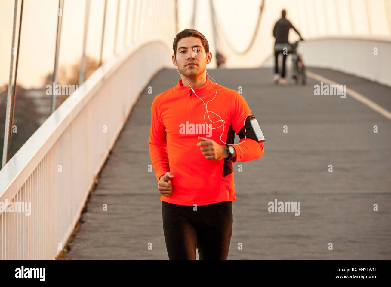 Runner maschio con cuffie jogging oltre il ponte Immagini Stock