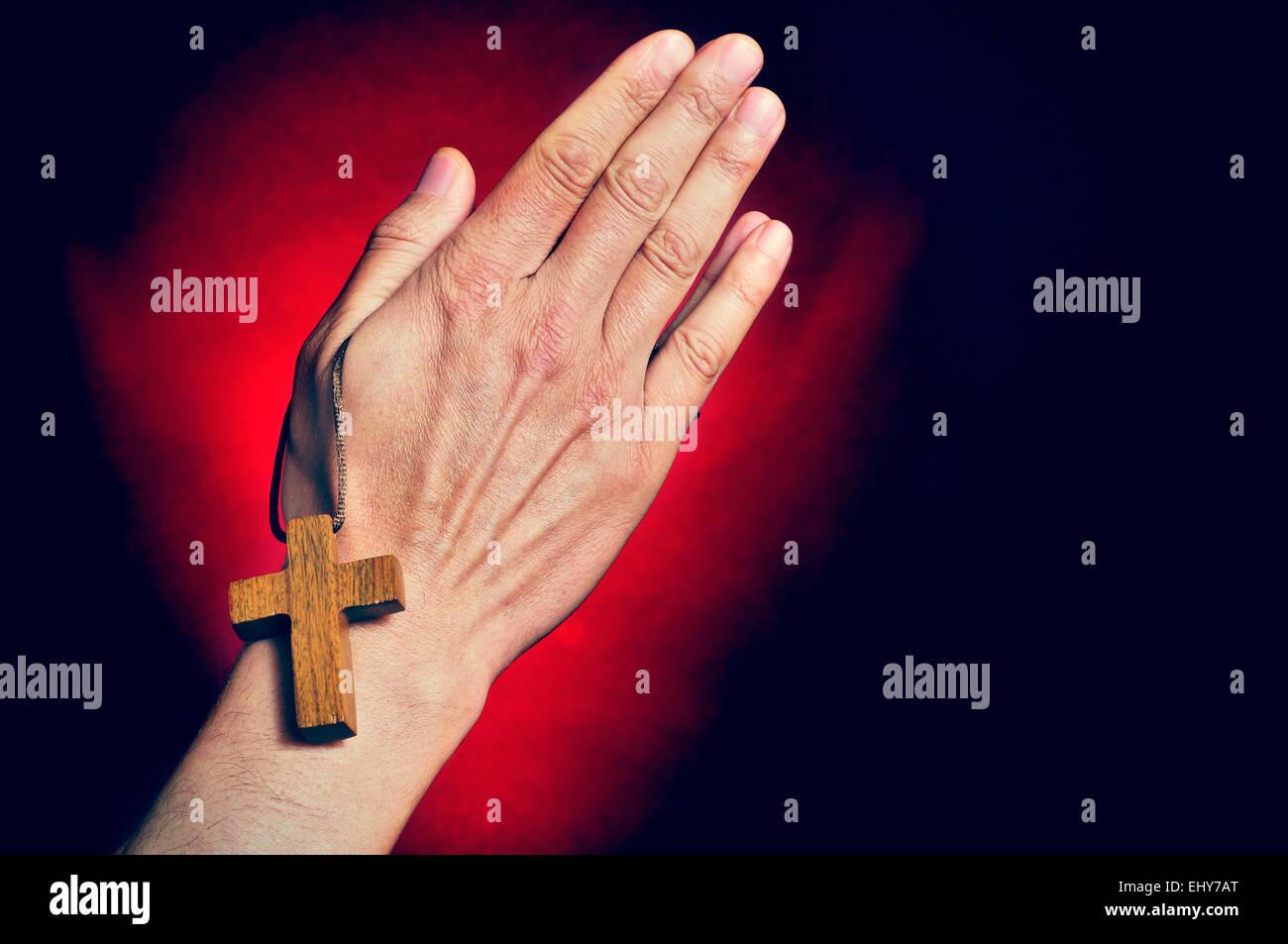 Primo piano di un giovane uomo che prega con una croce di legno nelle sue mani Immagini Stock