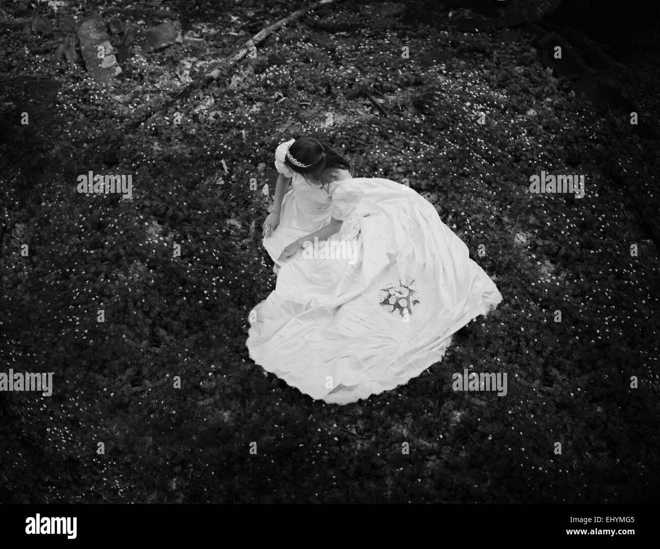 Vista aerea di una giovane donna seduta sul pavimento di foresta Immagini Stock