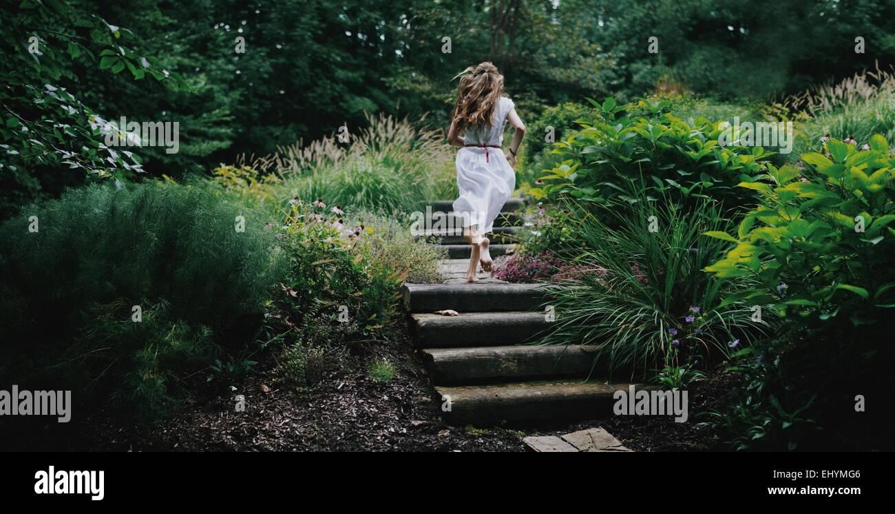 Vista posteriore della giovane donna in esecuzione su gradini in un giardino Immagini Stock