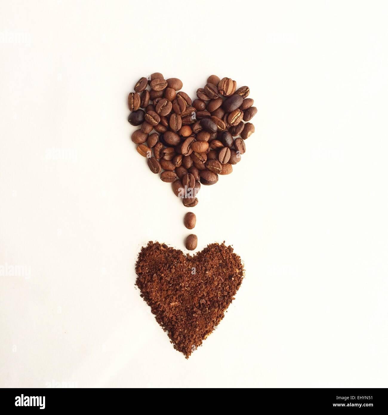 I chicchi di caffè in una forma di cuore, gocciolamento in un'altra forma di cuore di caffè macinato Immagini Stock
