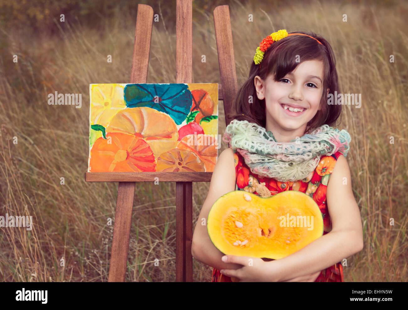 Ragazza seduta con la zucca da un dipinto di zucche Immagini Stock