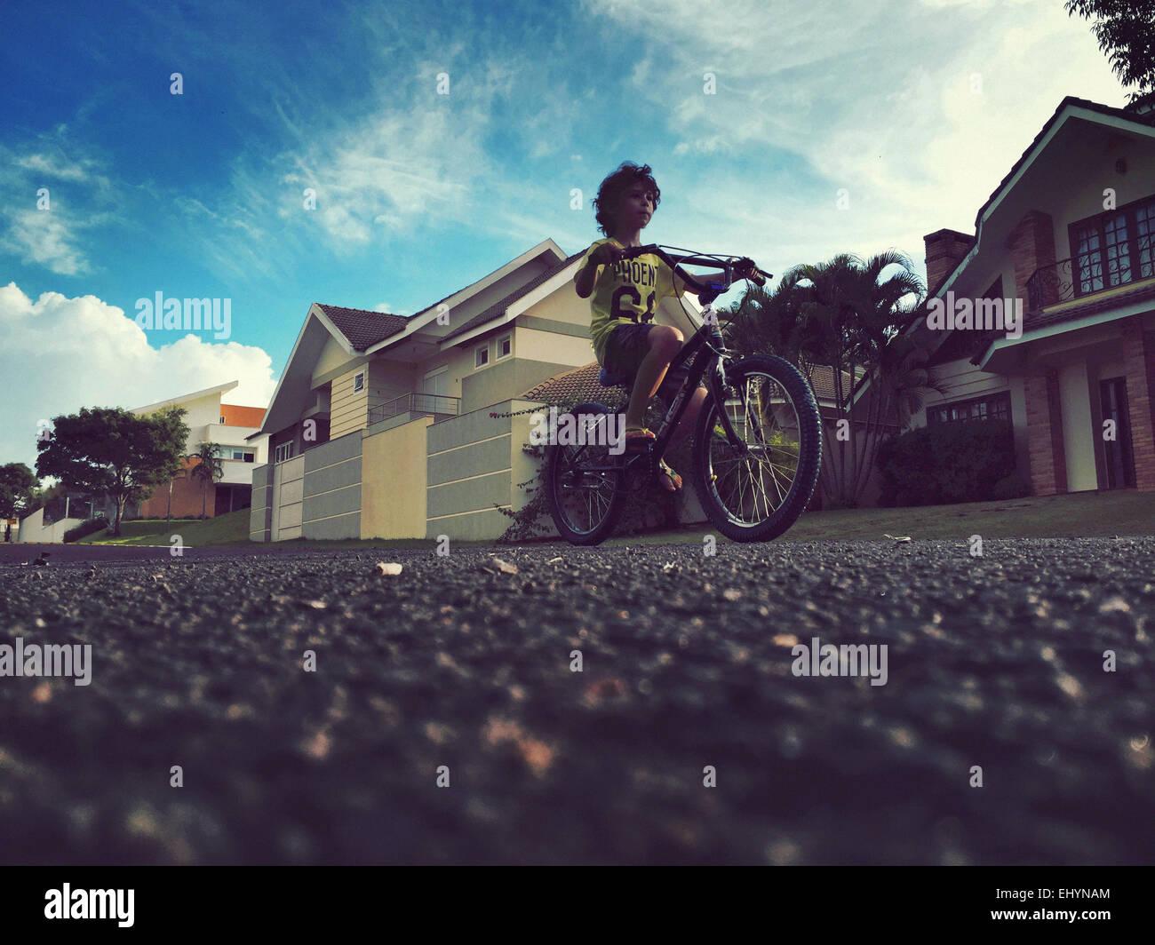 Basso angolo di visione di un ragazzo in bicicletta Immagini Stock