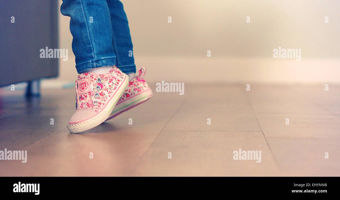 Baby girl imparare a stare sui suoi piedi Immagini Stock