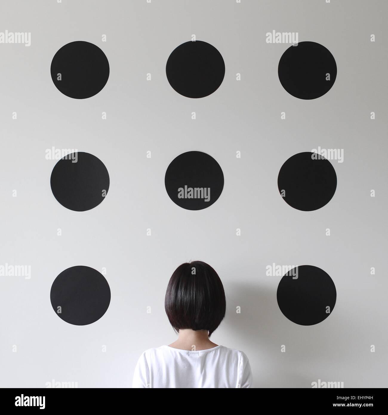 La donna di fronte a un muro con punti Foto Stock