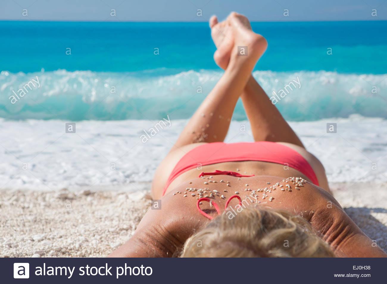 La donna, a prendere il sole con sabbia sul retro, di sunny beach Immagini Stock
