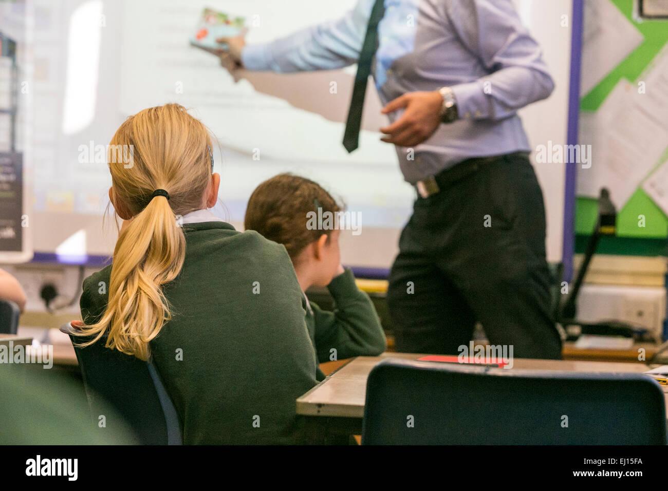 La scuola primaria le ragazze sono insegnate durante una lezione da parte di un insegnante maschio Immagini Stock