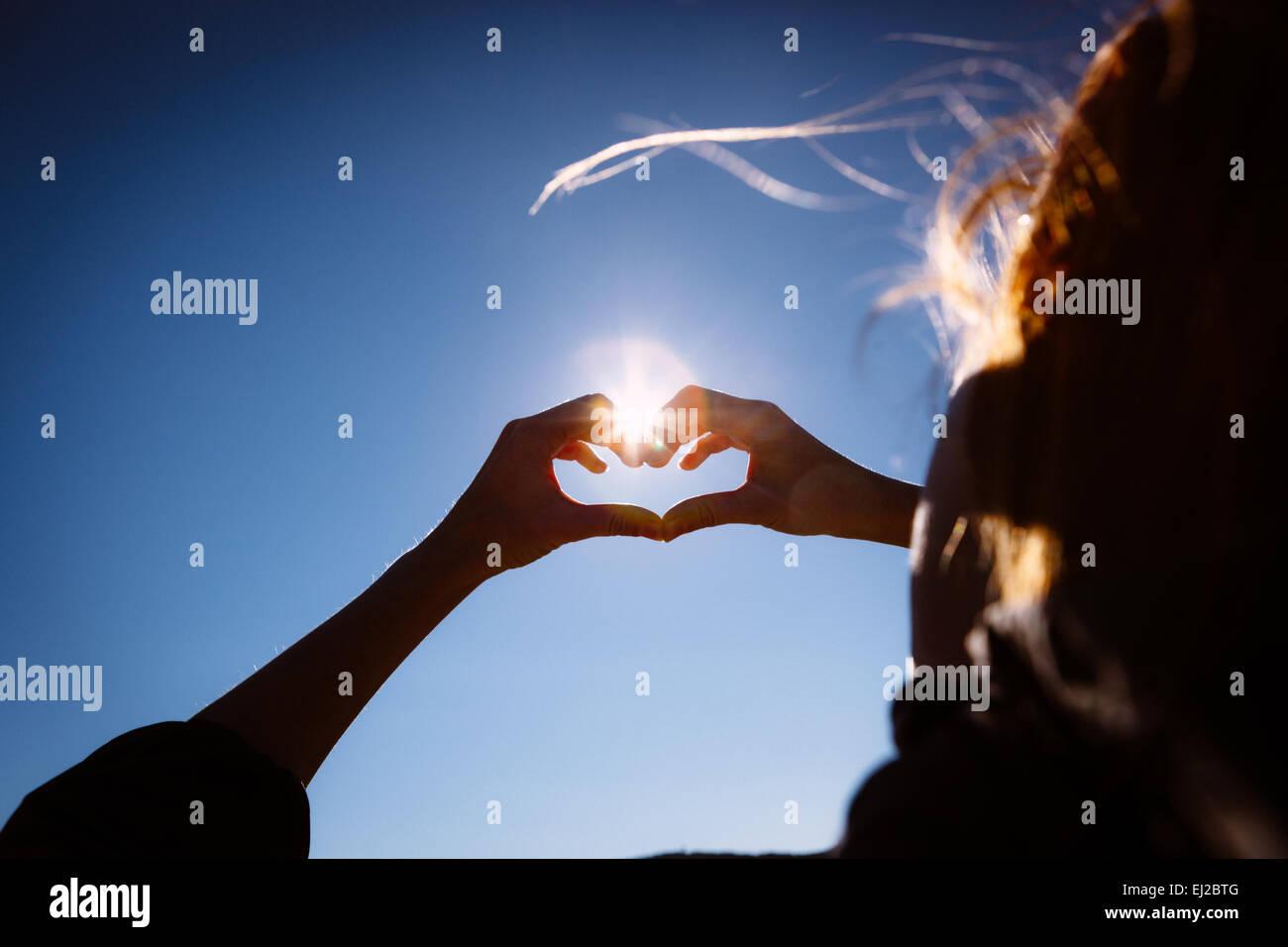 Le mani di fare l'amore segno di forma sul blu intenso del cielo. Immagini Stock