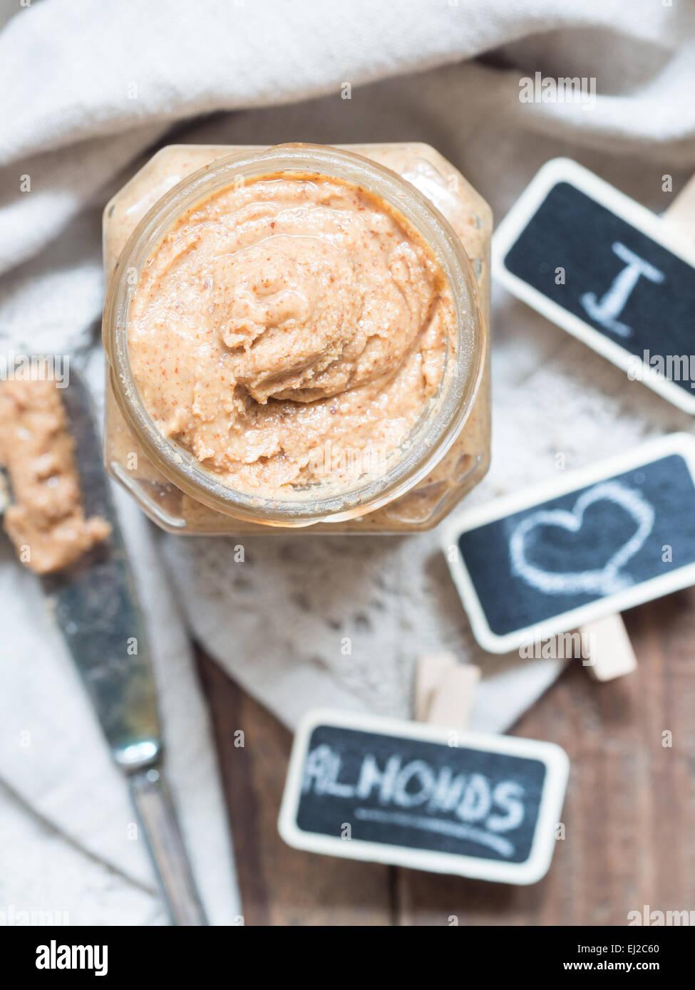 Foto verticale di prodotti naturali fatti in casa il burro di mandorle in un vaso di vetro posto sul rustico tavolo Immagini Stock