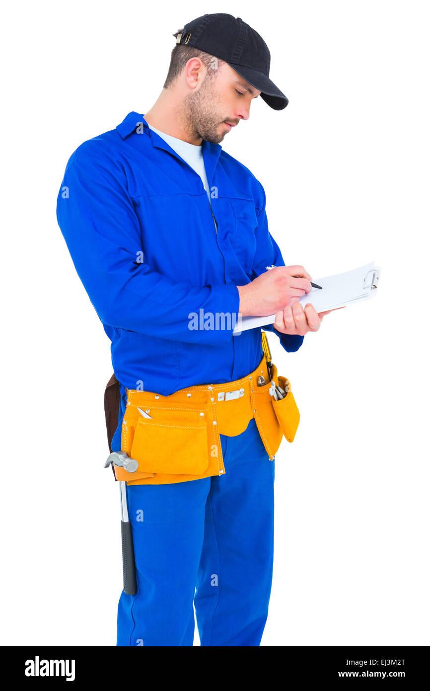 Tuttofare in tuta blu iscritto negli appunti Immagini Stock