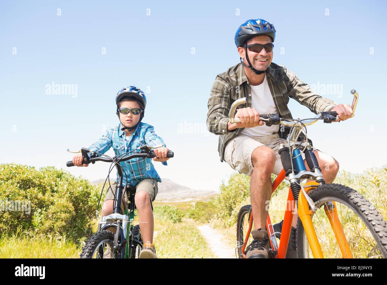 Padre e figlio in bici attraverso le montagne Immagini Stock