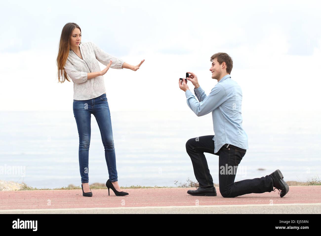 Proposta di rifiuto quando un uomo felice chiede in matrimonio con una donna sulla spiaggia Immagini Stock
