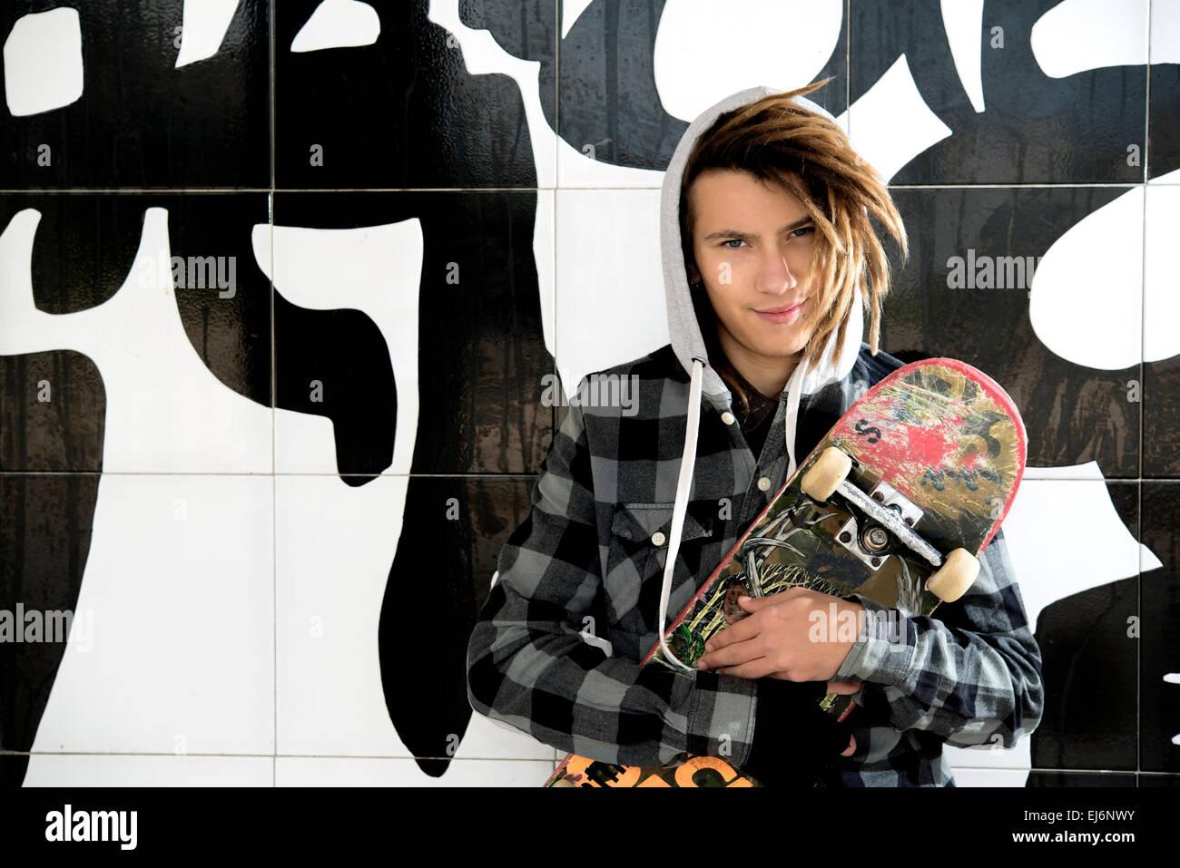 Ritratto di giovane ragazzo con skate e capelli rasta in un concetto di stile di vita Immagini Stock