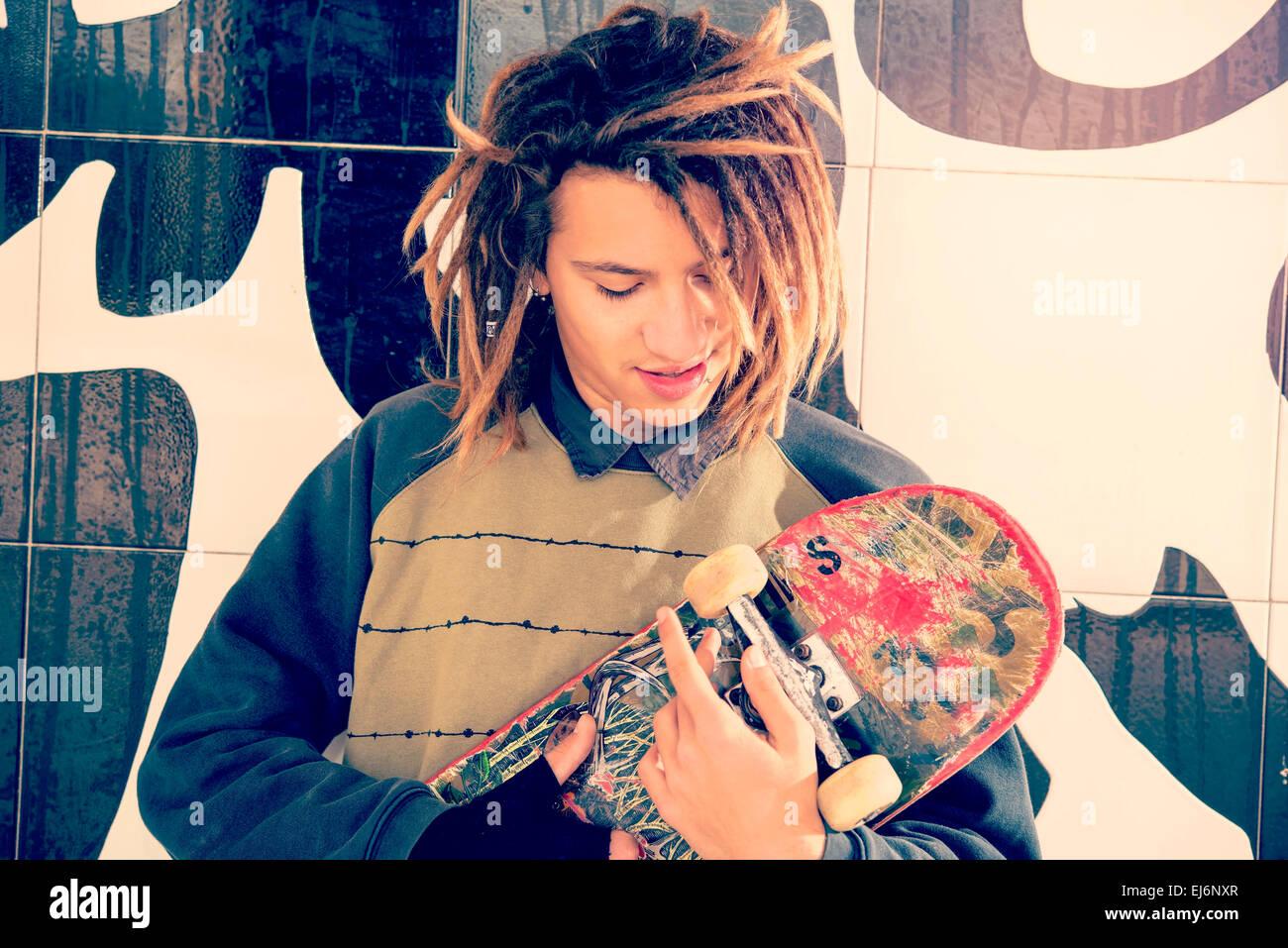 Ritratto di giovane ragazzo con skate e capelli rasta in un concetto di stile di vita caldo filtro applicato Immagini Stock
