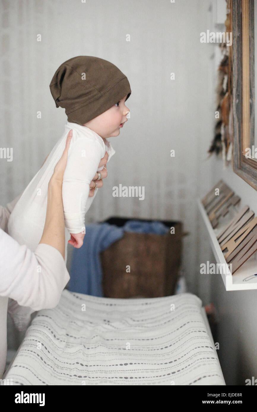 Un bambino che si terrà fino a guardare in uno specchio. Immagini Stock