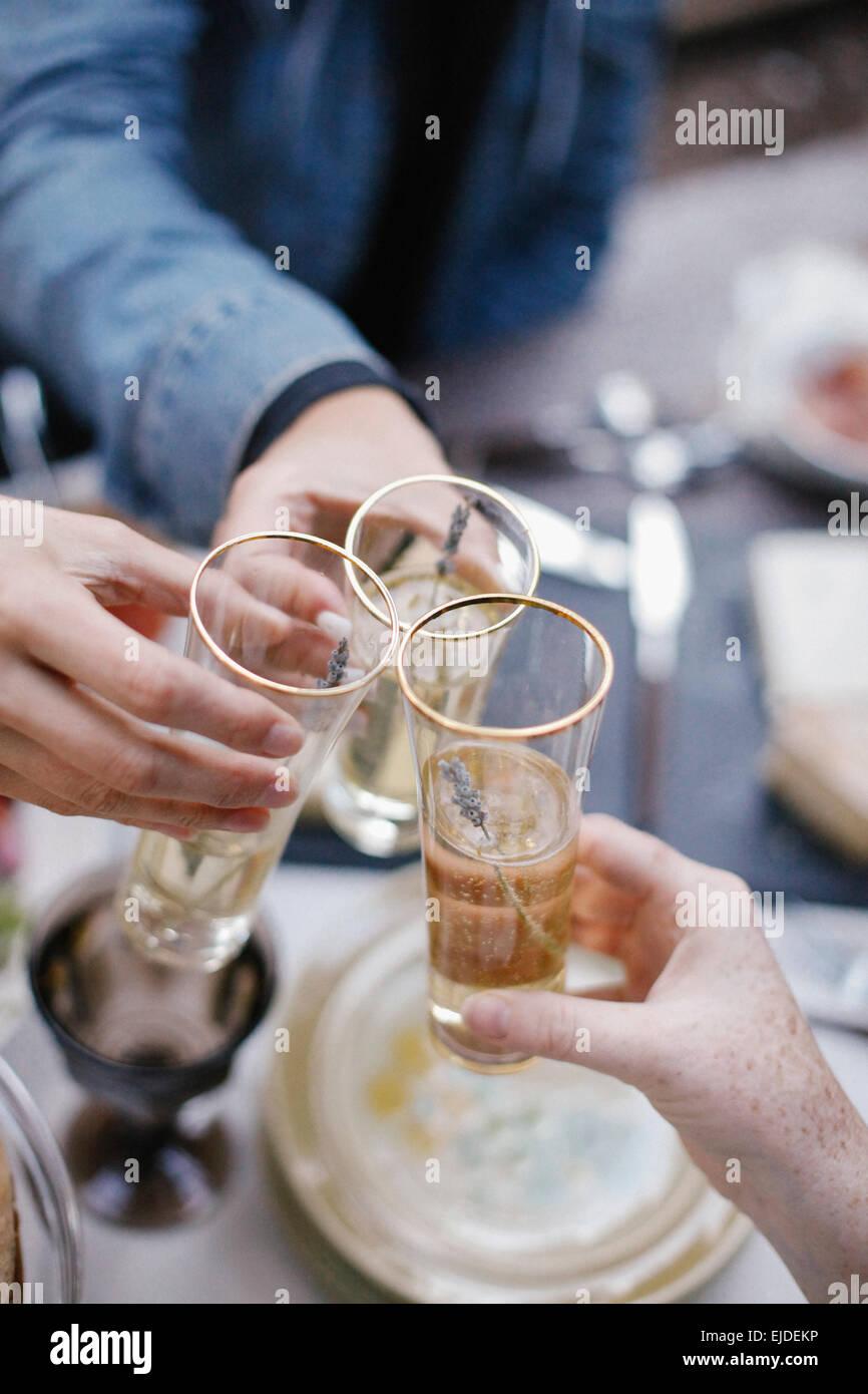 Tre persone che fanno un toast, bicchieri tintinnanti. Immagini Stock