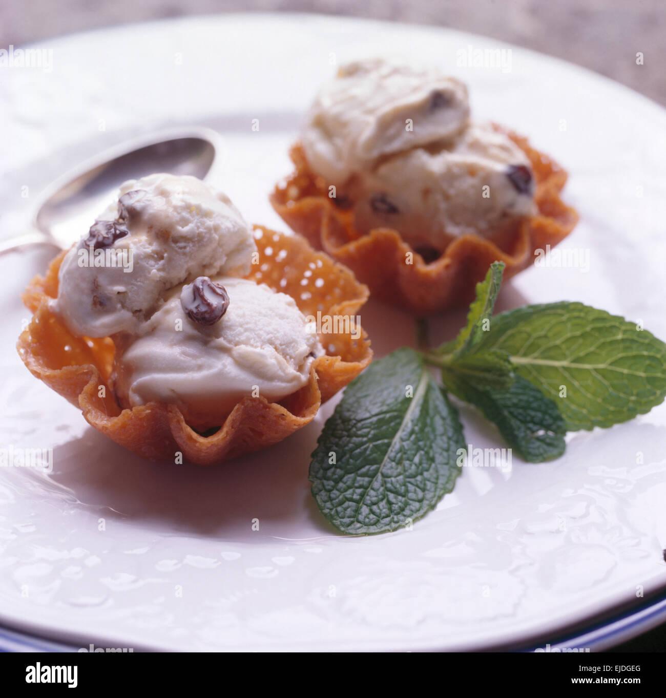 Close-up di brandy snap cesti riempiti con rum+raisin ice cream Immagini Stock
