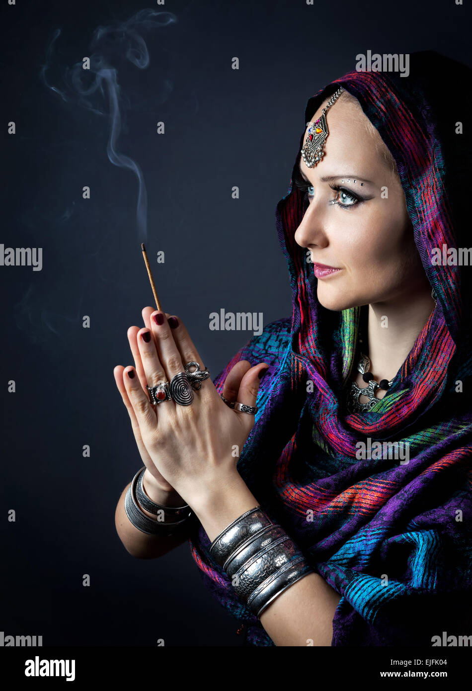 Donna avvolta in una sciarpa holding incenso stick in mani con Namaste gesto a sfondo scuro Immagini Stock