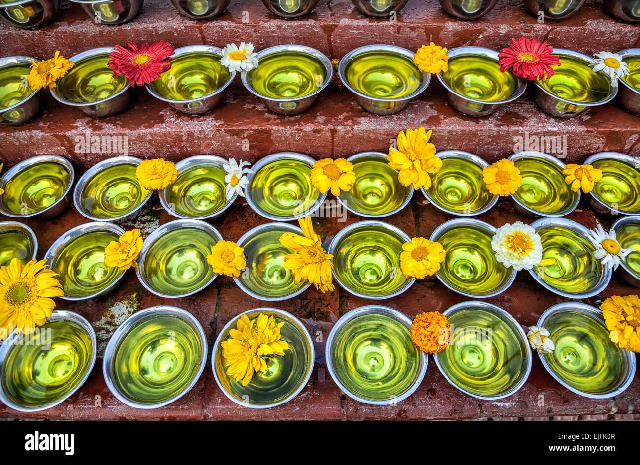 Ciotole con acqua con lo zafferano e fiori a Bodhnath stupa in valle di Kathmandu, Nepal Immagini Stock