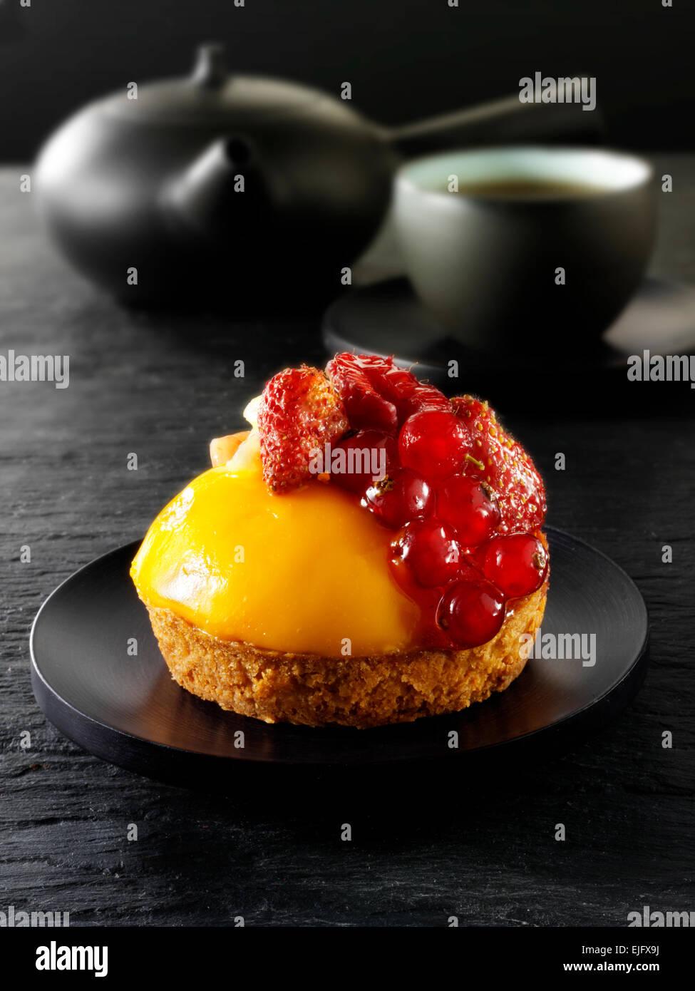 Caffè espresso, con ribes rosso e fragole crema pasticcera tart pasticceria in un cafè con tazza da tè Immagini Stock