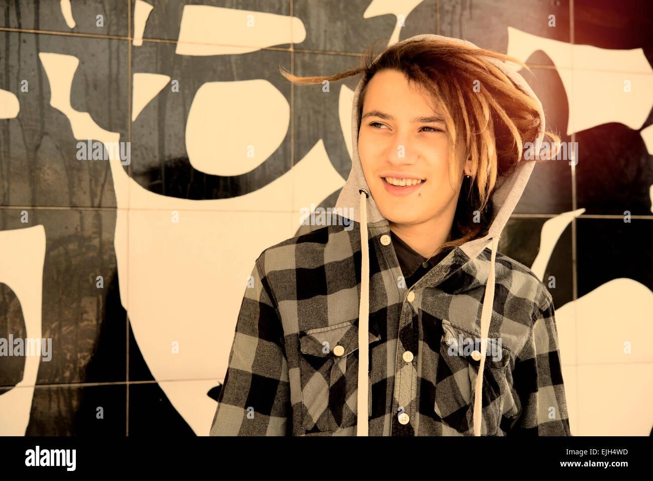 Ritratto di giovane ragazzo con capelli rasta in un concetto di stile di vita caldo filtro applicato Immagini Stock