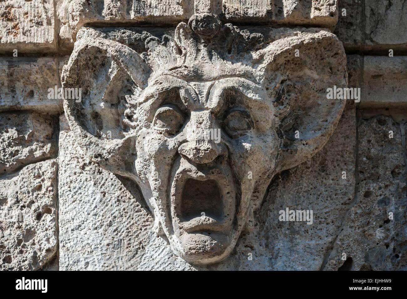 Stone carving, testa con enormi orecchie e bocca spalancata, Monaco di Baviera, Germania Immagini Stock
