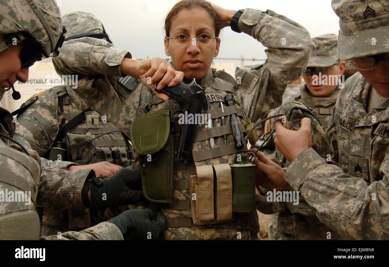 Noi soldati dell esercito assistere il personale sergente Enorita Marshall in corpo di serraggio armor prima di Immagini Stock