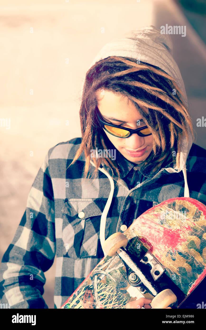 Ritratto di giovane ragazzo con lo skateboard e capelli rasta messa a fuoco selettiva in un concetto di stile di Immagini Stock