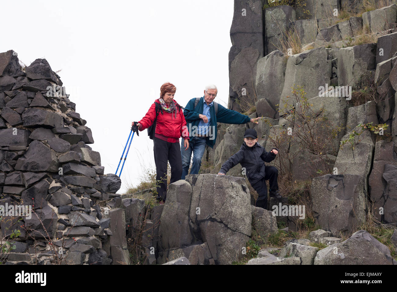 Coppia senior e bambino ragazzo trekking sul terreno roccioso. Immagini Stock