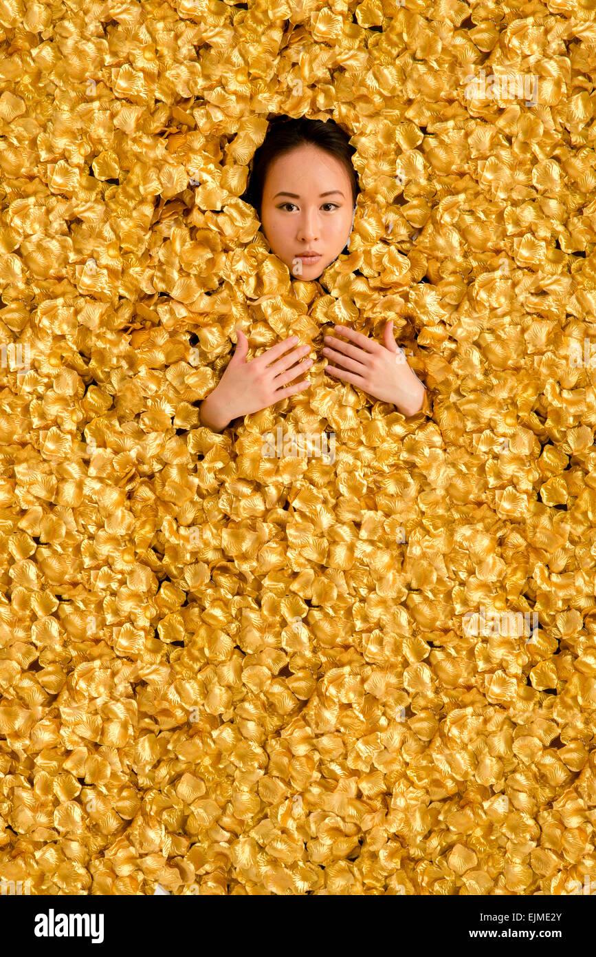 Lusso: un giovane di etnia cinese donna ragazza distesa in un bagno circondato racchiusi da migliaia di golden petali Immagini Stock