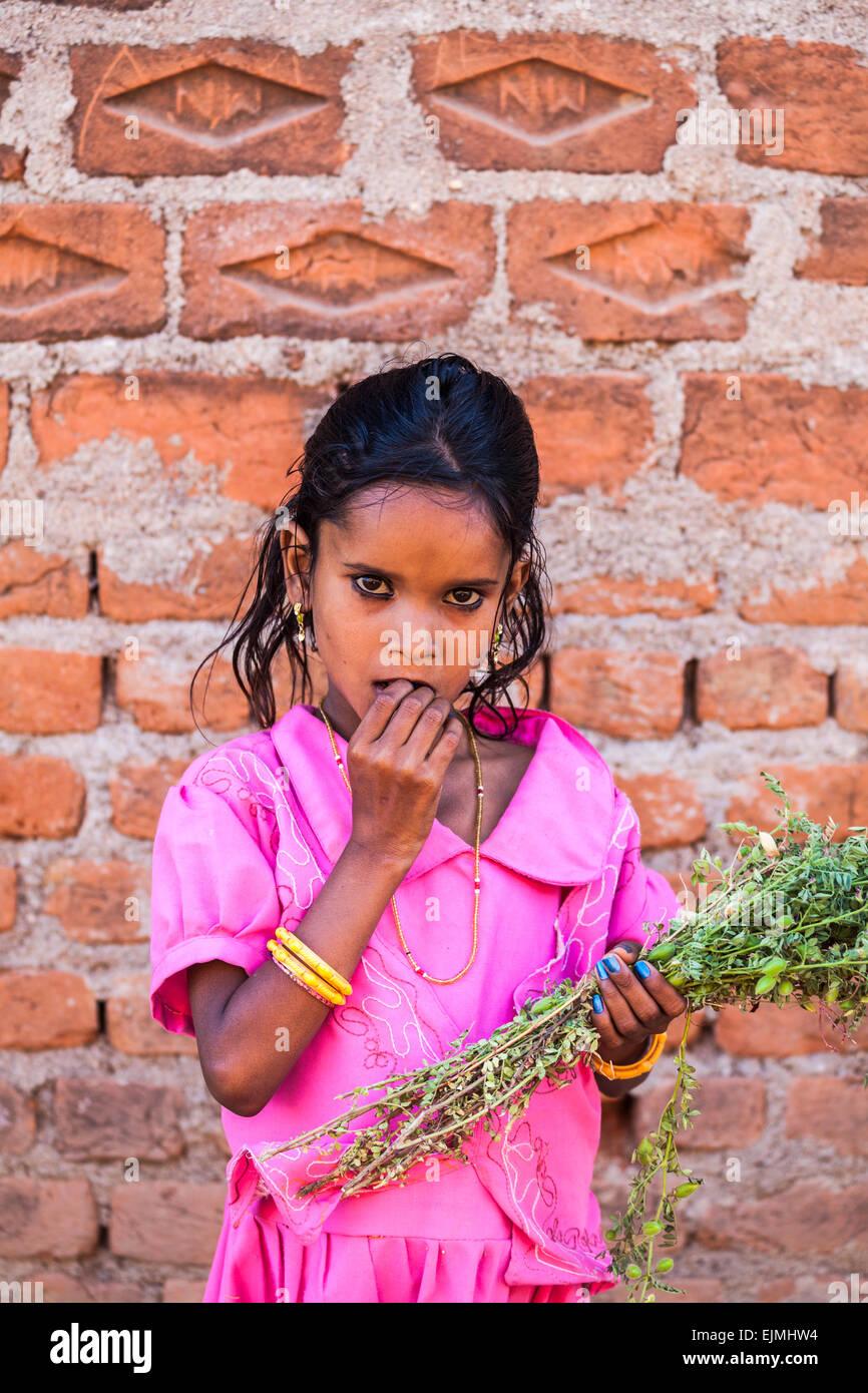Piuttosto giovane ragazza indiana con grandi occhi marroni e un abito rosa tenendo un mazzo di fiori, Khajuraho, Immagini Stock
