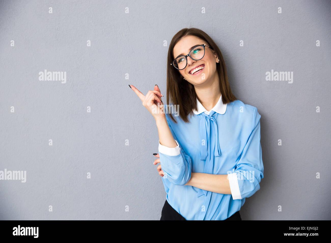 Allegro imprenditrice rivolto lontano su sfondo grigio. Indossare in maglietta blu e bicchieri. Guardando lontano Immagini Stock