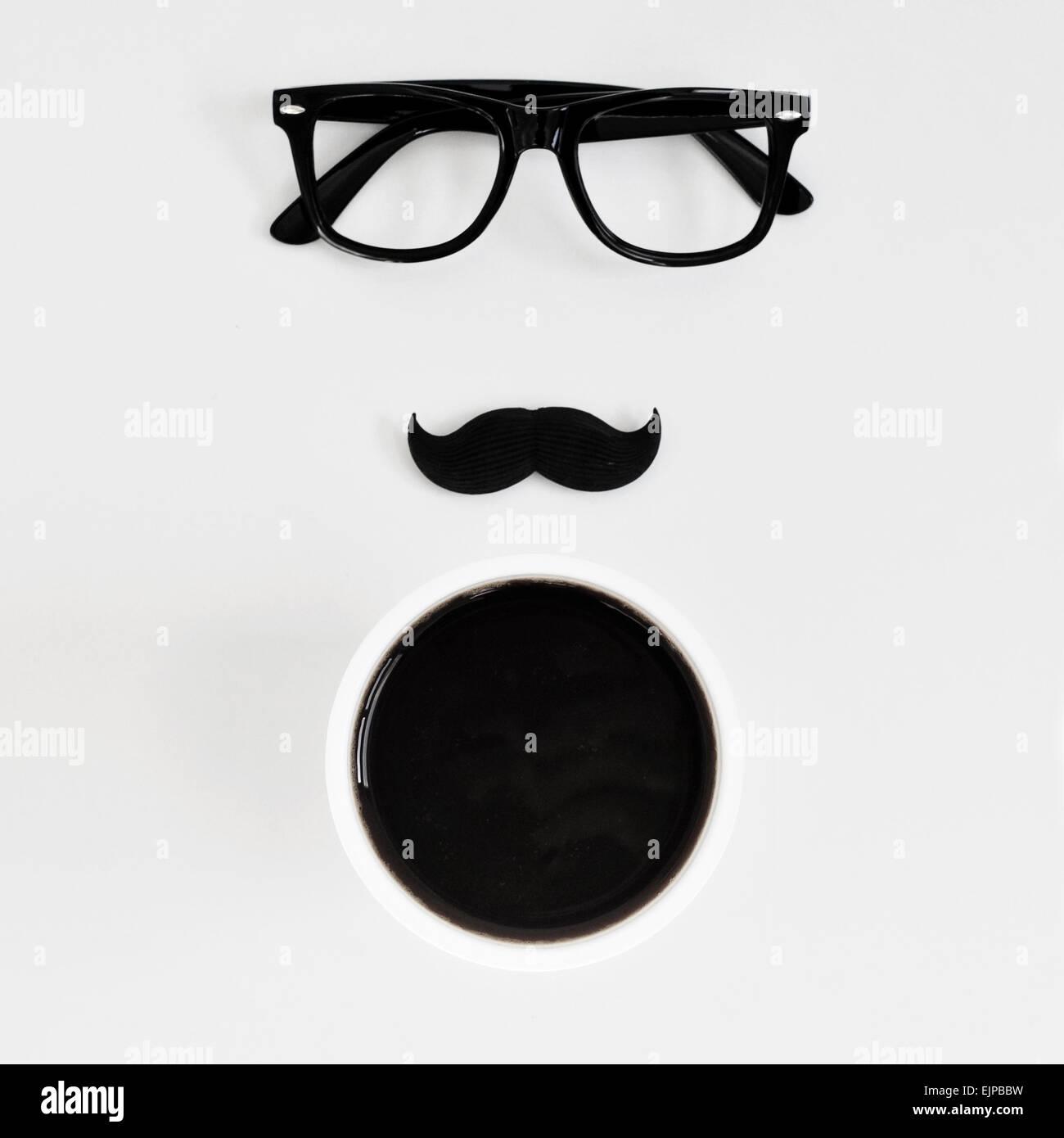 Alta angolazione di un tavolo bianco con una coppia di plastica nera cerchiati di occhiali, un baffi finti e una Immagini Stock